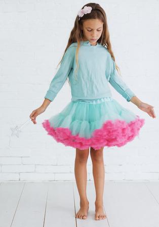 Studio portrait of cute little princess girl wearing holiday candy tutu skirt holding magic wand Stock Photo