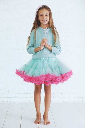 Studio portrait of cute little princess girl wearing holiday candy tutu skirt holding magic wand Фото со стока