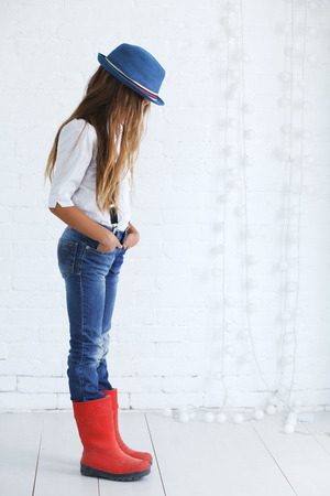 Cute teenage girl 8-9 years old wearing trendy hipster clothes posing over white brick wall