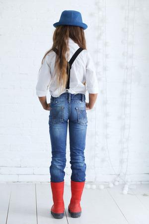かわいい十代の少女 8-9 歳白いレンガ壁を越えてにポーズ流行のヒップスターの服を着て