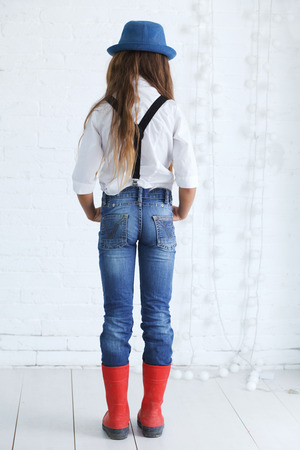 youth background: Cute teenage girl 8-9 years old wearing trendy hipster clothes posing over white brick wall