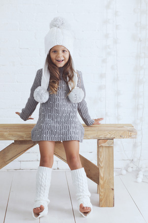 Cute little girl 5 years old wearing knitted trendy winter clothes posing over white brick wall