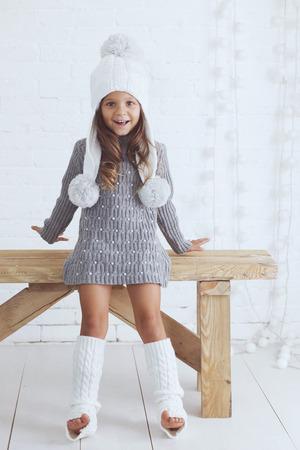 petite fille avec robe: La petite fille mignonne de 5 ans portait tricoté vêtements à la mode d'hiver posant sur le mur de briques blanc