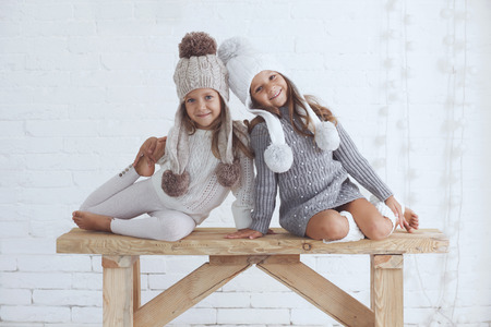 Cute little girls of 5 years old wearing knitted trendy winter clothes posing over white brick wall Reklamní fotografie