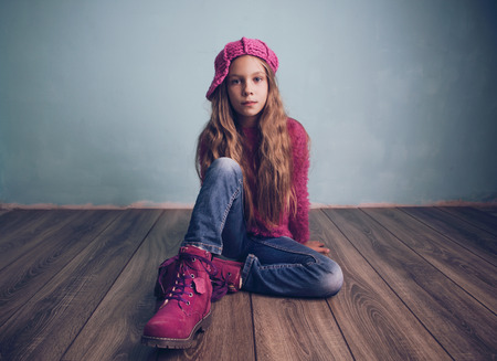 Cute pre-teen girl wearing fashion clothes and shoes sitting on wooden floor