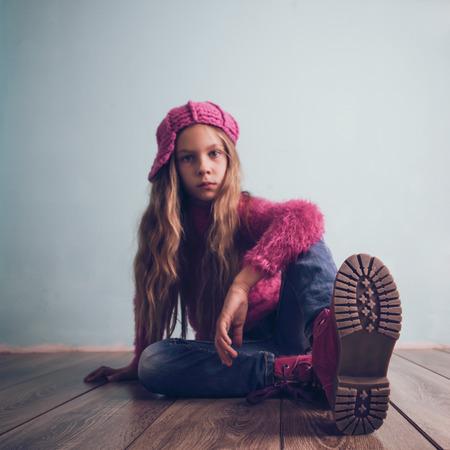 Cute pre-tiener meisje dragen mode kleding en schoenen zitten op houten vloer Stockfoto