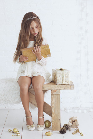 beautiful preteen girl: Portrait of luxury little princess reading a book in Christmas
