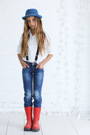 blue jeans kids: Cute teenage girl 8-9 years old wearing trendy hipster clothes posing over white brick wall