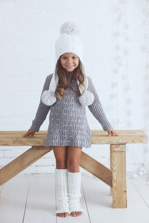 warmers: Cute little girl 5 years old wearing knitted trendy winter clothes posing over white brick wall