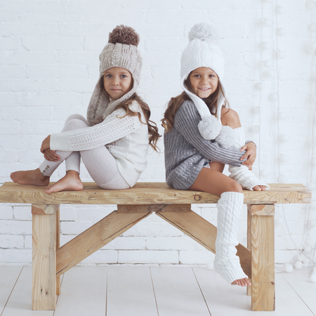 leg warmers: Cute little girls of 5 years old wearing knitted trendy winter clothes posing over white brick wall Stock Photo