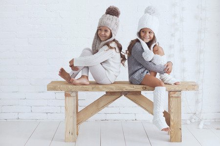 Cute little girls of 5 years old wearing knitted trendy winter clothes posing over white brick wall Stock Photo