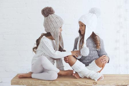 5 년 오래된 입고 귀여운 소녀 흰색 벽돌 벽에 포즈 유행 겨울 옷을 니트 스톡 콘텐츠