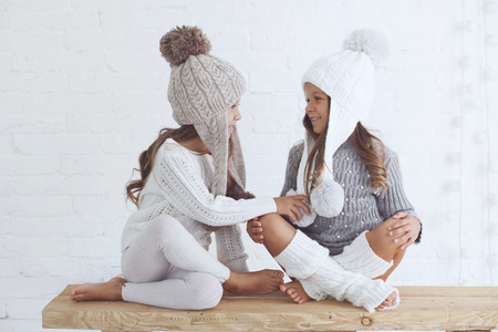 Cute little girls of 5 years old wearing knitted trendy winter clothes posing over white brick wall Фото со стока