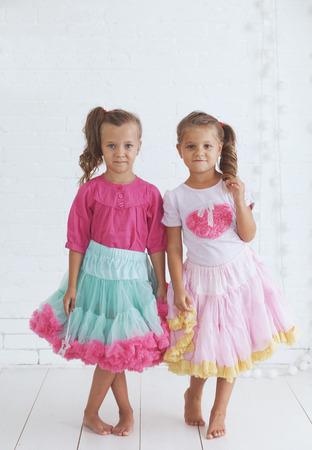 Studio portrait of two cute little princess girls wearing holiday candy tutu skirt holding magic wand