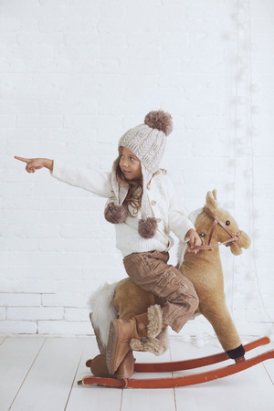 Cute little girl 5 years old wearing knitted trendy winter clothes posing over white brick wall photo