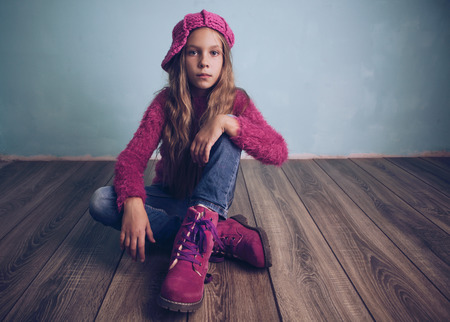 cool kids: Cute pre-teen girl wearing fashion clothes and shoes sitting on wooden floor
