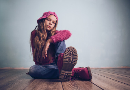 model posing: Cute pre-teen girl wearing fashion clothes and shoes sitting on wooden floor