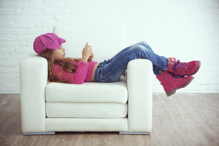beautiful preteen girl: Cute pre-teen girl wearing fashion winter clothes posing in white interior