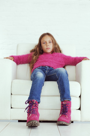 Cute pre-teen girl wearing fashion winter clothes posing in white interior, focus on shoes Stock Photo