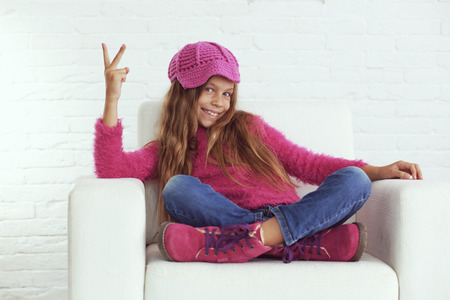 pink posing: Cute pre-teen girl wearing fashion winter clothes posing in white interior