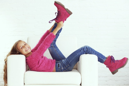 preteen girl: Cute pre-teen girl wearing fashion winter clothes posing in white interior