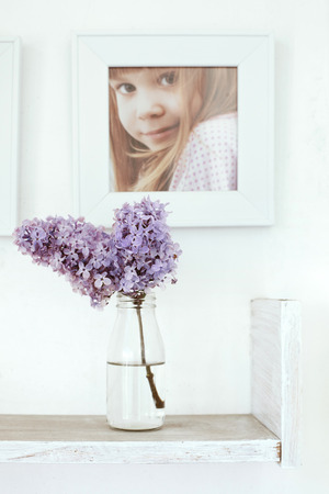 Small bouquet of lilac in glass bottle on white wooden shelf with photo frame on it as detail of interior photo
