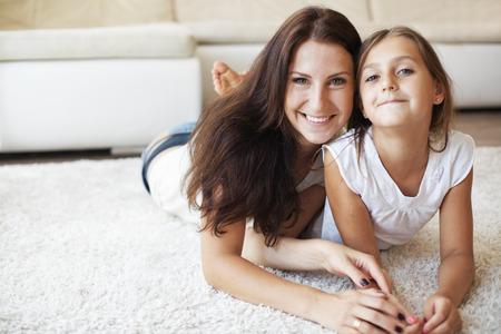 casita de dulces: Madre con su hija preadolescente que se divierte en una alfombra blanca en la sala de estar en casa