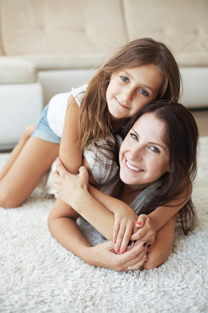 eight years old: Mother with her preteen daughter having fun on a white carpet in living room at home