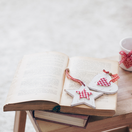Warm photo of cozy moments: vintage book with Christmas decor and candlestick on wooden bench, shallow focus.