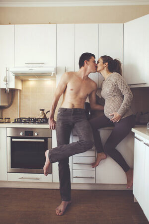 Romantic cozy home portrait of beautiful loving couple making coffee together at the kitchen at home photo
