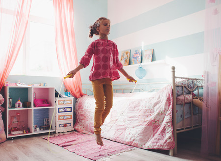 preteen girls: 8 years old girl jumping in a child room at home, still life photo