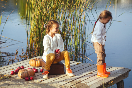 children pond: Two cheerful little girls playing on the lake in warm autumn day  Fall lifestyle portrait of children having fun on wooden bearth over the river landscape Stock Photo