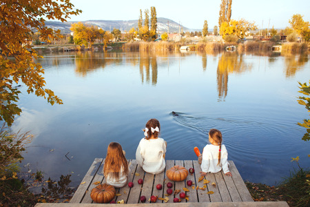 Three cheerful little girls playing on the lake in warm autumn day  Fall lifestyle portrait of children having fun on wooden bearth over the river landscape photo