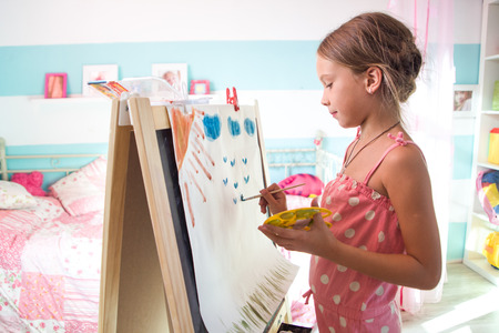 7-8 years old child drawing on easel in child room at home photo