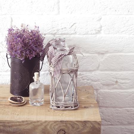 소박한 가정 장식, 프로방스 스타일. 나무 벤치에 건조 필드 꽃과 유리 스파이스 항아리의 라벤더 꽃다발입니다.