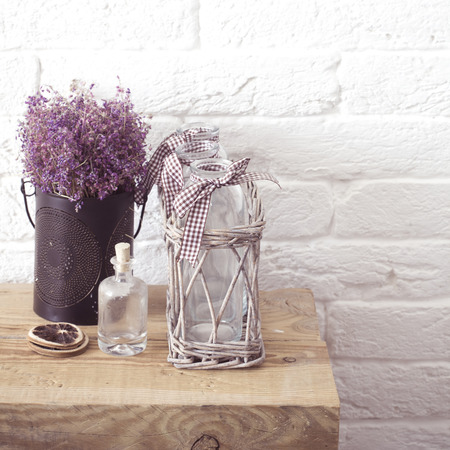 detail: Rustic home decor, provence style. Lavender bouquet of dried field flowers and glass spice jars on wooden bench.