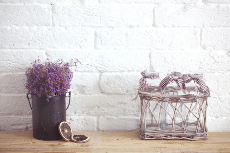 aromas: Rustic home decor, provence style. Lavender bouquet of dried field flowers and glass spice jars on wooden bench.