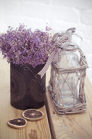Rustic home decor, provence style. Lavender bouquet of dried field flowers and glass spice jars on wooden bench. photo