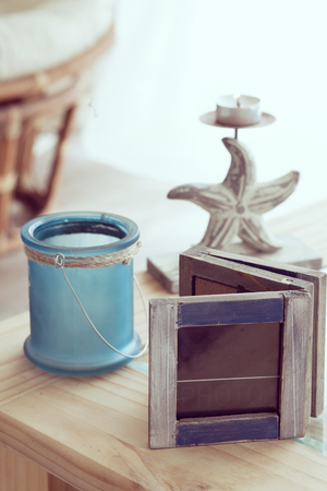 idea comfortable: Idea of interior decor in beach cottage style with trendy glass candlestick and rustic photo frame.