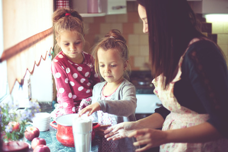 twin sister: Mother with her 5 years old kids cooking holiday pie in the kitchen, casual lifestyle photo series in real life interior