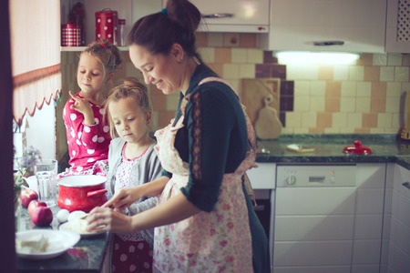 parenthood: Mother with her 5 years old kids cooking holiday pie in the kitchen, casual lifestyle photo series in real life interior