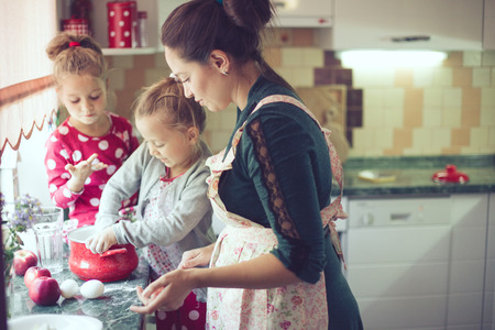 making: Mother with her 5 years old kids cooking holiday pie in the kitchen, casual lifestyle photo series in real life interior