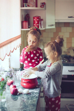 5 years old twins cooking holiday pie in the kitchen, casual lifestyle photo series in real life interior photo