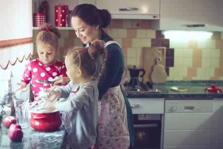 キッチンでは、実際の生活のインテリアでカジュアルなライフ スタイルの写真シリーズ ホリデイ ・ パイを調理彼女の 5 歳の子供を持つ母