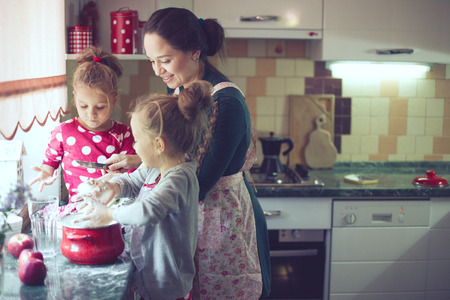 lifestyle: Mother with her 5 years old kids cooking holiday pie in the kitchen, casual lifestyle photo series in real life interior