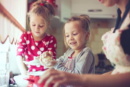 niñas gemelas: Madre con sus 5 años de edad los niños de cocina pastel de fiesta en la cocina, estilo de vidas foto casual en el interior de la vida real