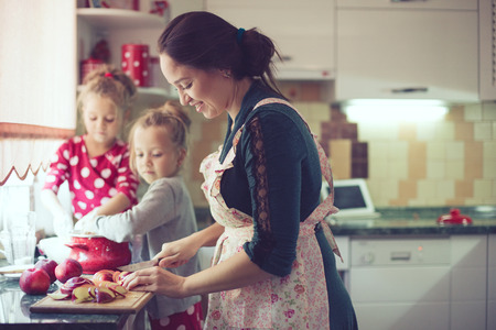 family of five: Mother with her 5 years old kids cooking holiday pie in the kitchen, casual lifestyle photo series in real life interior