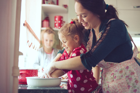 ni�as gemelas: Madre con sus 5 a�os de edad los ni�os cocinar pastel de d�a de fiesta en la cocina, estilo de vida serie foto casual en el interior de la vida real
