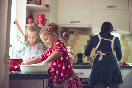 making fun: Mother with three kids cooking holiday pie in the kitchen, casual lifestyle photo series in real life interior