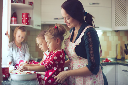 Mother with three kids cooking holiday pie in the kitchen, casual lifestyle photo series in real life interior photo